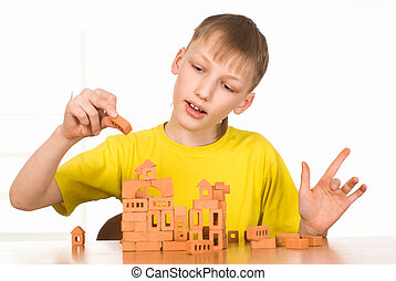 young boy constructing on a white background