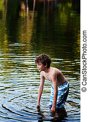 young boy cooling off in a lake on a hot summer day