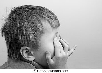 Young boy covering face.