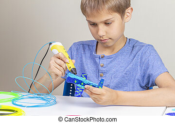 Young boy creating with 3d printing pen new object