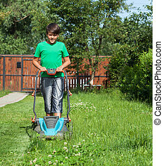 Young boy cutting the grass with a lawn mower