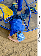 Young boy drawing a circle in the sand
