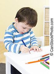 Young boy draws with a blue pencil