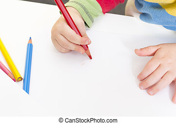 Young boy draws with a red pencil