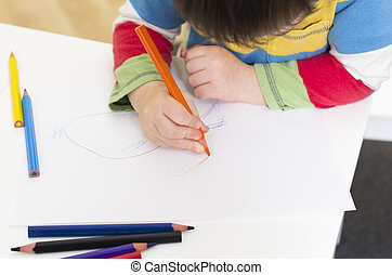 Young boy draws with an orange pencil