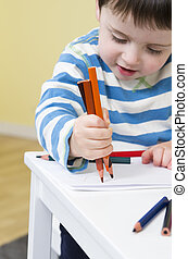 Young boy draws with three pencils