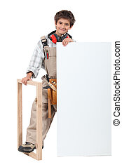 Young boy dressed as a carpenter with a board left blank for your message