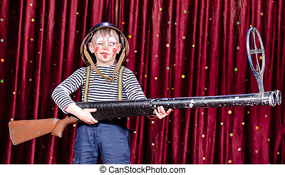 Young Boy Dressed as Clown Holding Oversized Rifle