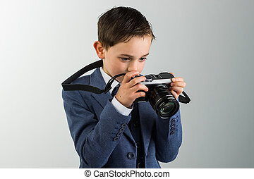 Young boy dressed up with photo camera