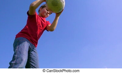 Young boy dribbles the ball against blue sky, slow motion