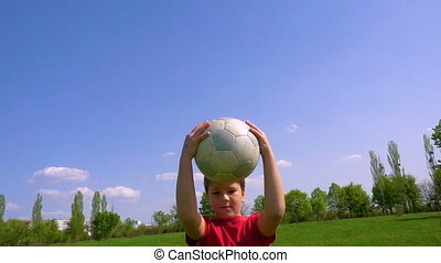 Young boy dribbles the ball on green meadow, slow motion