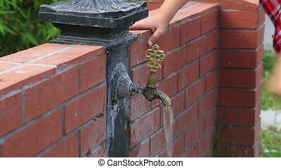 Young boy drinking water from faucet in the garden