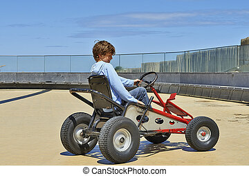 Young boy driving a Quadricycle at the north sea in Belgium