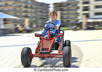 Young boy driving a Quadricycle, motion blur
