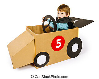 Young boy driving his cardboard car