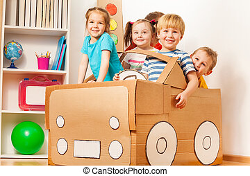 Young boy driving his friends in cardboard car