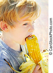 Young boy eating a grilled ear of corn