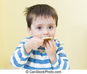 Young boy eating a pikelet