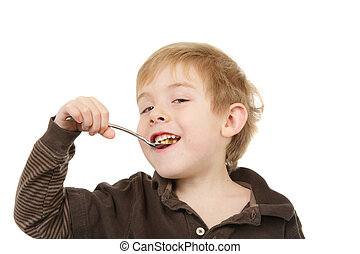 Young boy eating a spoonful of cereal