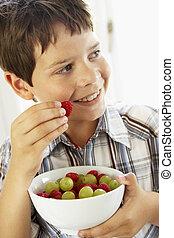 Young Boy Eating Bowl Of Fresh Fruit