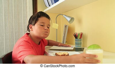 Portrait of a school boy studying Eating cake and drinking milk