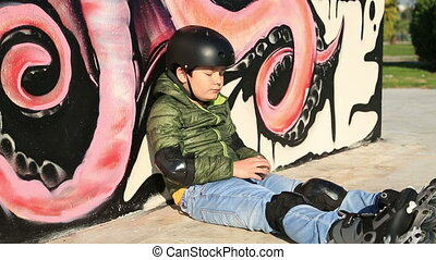 Child with roller skate and protective clothing eating chips outdoor