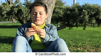 Young boy eating croissant at the outdoors - Portrait of a...