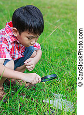 Young boy exploring nature with magnifying glass. Outdoors in the day time.