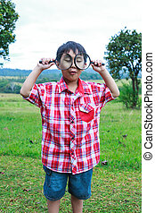 Young boy exploring nature with magnifying glass. Outdoors.