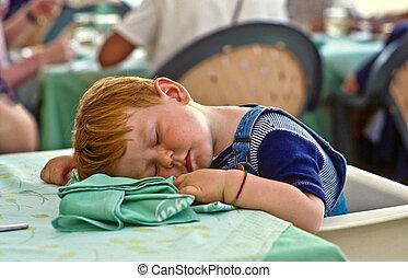 boy falling asleep on the dinner table