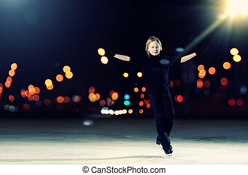 Young boy figure skating at sports arena
