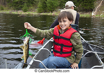 A young boy fisherman in a canoe holds up the first walleye of the day
