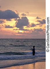 Young Boy Fishing - A boy fishing at the ocean.