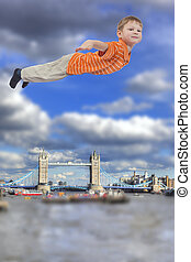 Young boy flying with Tower bridge, London, UK in background