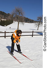 young boy for first time with cross-country skiing in the mountains in winter