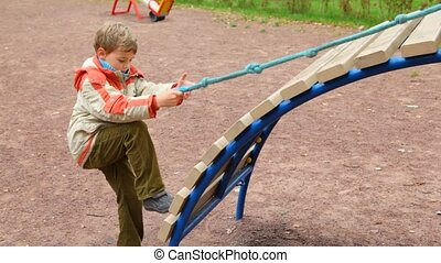 young boy gets on slide by means of cord in children ...