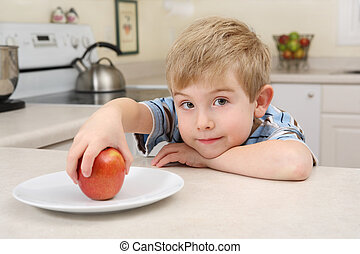 Young boy getting an apple for a snack