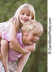 Young boy giving young girl piggyback outdoors smiling
