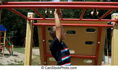 Young Boy Hang on Monkey Bars by his Hands to Exercise at Outdoor Playground against the Sky in Slow Motion