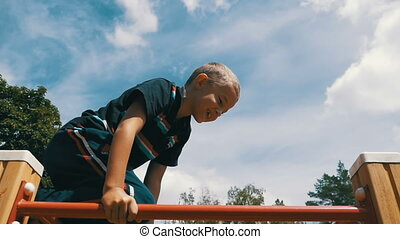 Young Boy Hang the Bar by his Hand to Exercise at Outdoor...