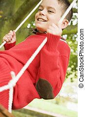Young boy having fun on swing