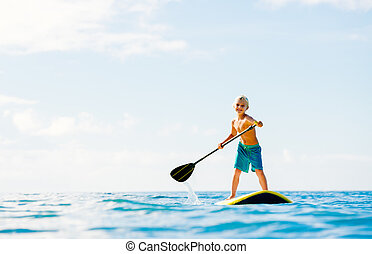 Young Boy Having Fun Stand Up Paddling in the Ocean