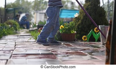 Young boy helps family cleaning the tile using a mop in...