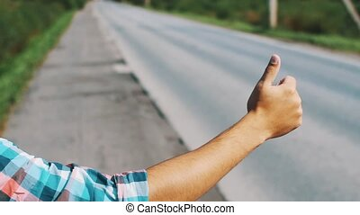 Young boy hitchhiking at road in summer sunny day. Journey. Thumb up. Traveling