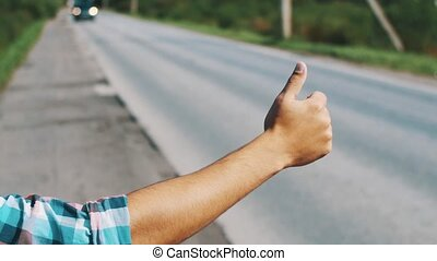 Young boy hitchhiking at road in summer sunny day. Tourist. Thumb up. Cars.
