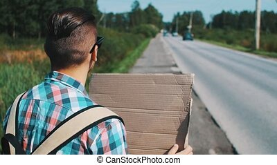Young boy hitchhiking at road with cardboard plate in summer sunny day. Travel.