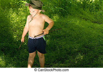 Young boy holding a stick strolling by the nature