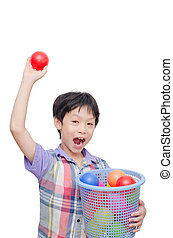 Young boy holding plastic ball over white