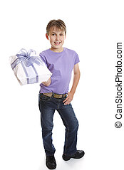 Young boy holding present - A young boy dressed in jeans and...