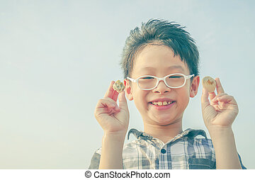 boy holding shell over sky background